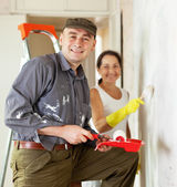 Man and woman paints wall — Stock Photo