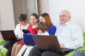 Multigenerations family with electronic devices at home — Stock Photo