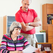 Mature couple reading financial document — Stock Photo #38555537