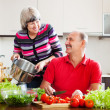 Happy married mature couple cooking in kitchen — Stock Photo