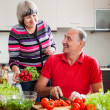 Senior man and mature woman cooking vegetables — Stock Photo