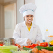 Stock Photo: Cook works with vegetables at commercial kitchen
