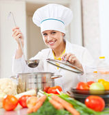 Happy young cook tests vegetarian food — Stock Photo