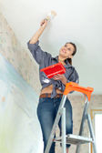 Woman paints ceiling — Stock Photo