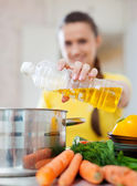 Woman pouring oil from bottle into the saucepan — Stock Photo