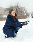 Happy girl throwing up snowflakes — Stock Photo
