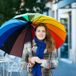 Beauty girl with umbrellin autumn street — Stock Photo #38571319