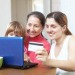 Happy family paying by credit card in internet — Stock Photo