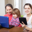 Happy family with electronic devices at home — Stock Photo
