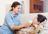 Woman caring for sick mature mother — Stock Photo