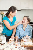 Cooking mother with adult daughter — Stock Photo