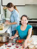 Two smiling women making vareniki with berries — Stock Photo