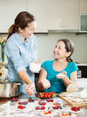 Happy mother with daughter making berries dumplings — Stock Photo
