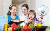 Happy women cook vegetables in kitchen — Stock Photo