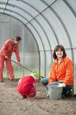 Kvinnor med barn fungerar på drivhus — Stockfoto