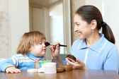 Grandmother putting facepowder on face of girl — Stock Photo