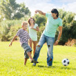 Parents with child playing with soccer ball — Stock Photo