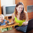 Happy young mother working with laptop and baby — Stock Photo
