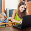 Sorehead mother with baby using laptop — Stock Photo #38694063