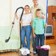 Family dusting with vacuum cleaner — Stock Photo