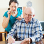 Wistful mature couple reading documents — Stock Photo