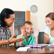 Smiling parents helping with homework — Stok fotoğraf