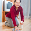 Stock Photo: Happy mature womrubbing wooden floor