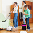 Family with teenage boy cleaning in living room — Stock Photo #38694211