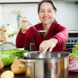 Mature womadding seasoning into lent diet soup — Stock Photo #38694527