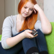 Stock Photo: Red-haired teenager girl waits telephone call