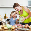 Happy mother with baby cooking — Stock Photo
