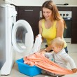 Family woman putting clothes in to washing machine — Stock Photo #38694733