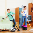 Happy family of three cleaning in living room — Stock Photo