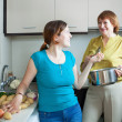 Stock Photo: Mature womand adult daughter cooking food