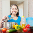 Smiling mature housewife with vegetables — Stock Photo #38695119