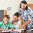 Couple with teenager schoolboy doing homework — Stock Photo #38695261