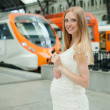 Smiling pregnant woman waiting train — Stock Photo