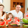 Smiling happy family together with watermelon over dining table — Stock Photo