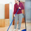 Stock Photo: Mature housewife with dustpand brush at home