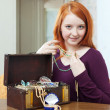 Stock Photo: Red-headed girl tries necklace in home