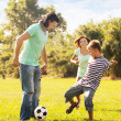 Happy parents with teenage son playing with ball — Stock Photo #38695467