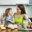 Happy woman with baby cooking at kitchen — Stock Photo