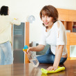 Stock Photo: Womwith husband cleaning living room