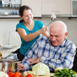 Happy playing mature couple cooking food — Stock Photo #38695749