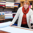 Stock Photo: Mature saleswommeasures fabric