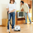 Stock Photo: Woman and man doing housework together