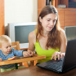 Woman working with laptop and baby — Stock Photo