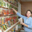 Stock Photo: Saleswomwith seeds at store
