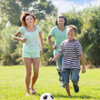 Family of three playing in soccer — Stock Photo #38695877