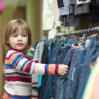 Child chooses jeans at shop — Stock Photo #38695953